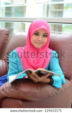 Young asian muslim woman in head scarf smile reading magazine - stock photo