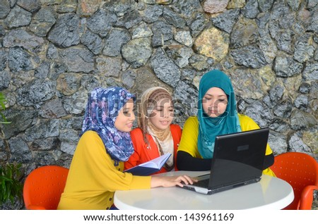 Young asian muslim woman in head scarf smile while surf internet - stock photo