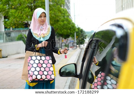 Young asian muslim woman in head scarf smile with car - stock photo