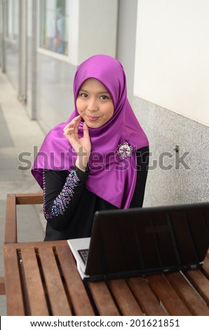 Young asian muslim woman in head scarf smile with mobile tablet - stock photo