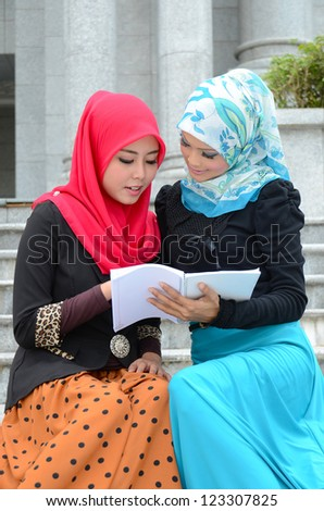Young asian muslim woman in head scarf smile with note book