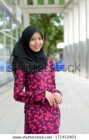 Young asian muslim woman in head scarf with happy pose - stock photo