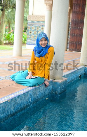 Young asian muslim woman in head scarf with stylish beautiful dress at recreation park - stock photo