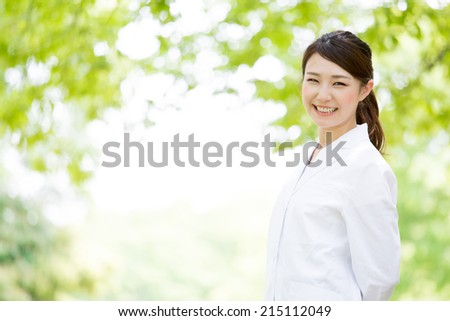 young asian nurse relaxing in the park - stock photo