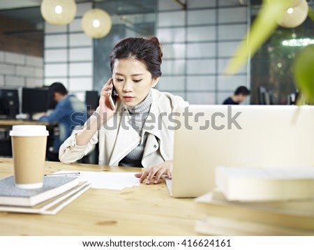 young asian office worker sitting at desk calling using mobile phone in office. - stock photo