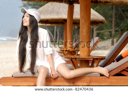 young asian pretty girl relaxing at beach to enjoy the leisure time - stock photo