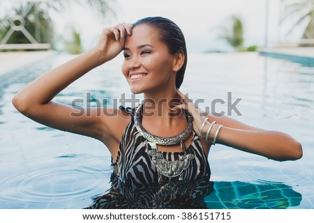 young asian sexy beautiful woman in tropical dress, zebra print, posing in pool, smiling, happy, drops of water on skin, ethnical necklace, wet hair, summer vacation, tanned skin - stock photo
