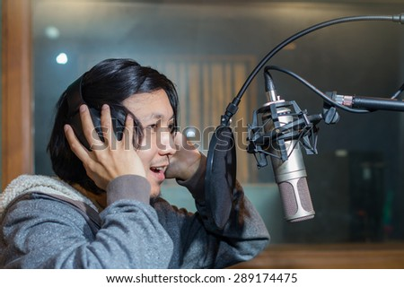 Young Asian singer recording a song with microphone in music studio - stock photo