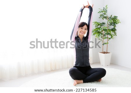 young asian sporty woman stretching in the room - stock photo