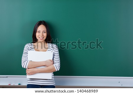 young asian student holding binder and leaning against board - stock photo