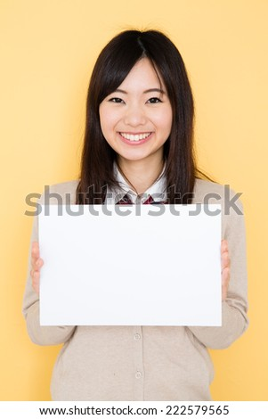 young asian student isolated on yellow background - stock photo