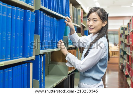 Young asian student picking a book from the bookshelf - stock photo