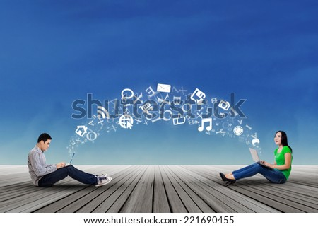 Young asian student sitting outdoors and share information with laptop computer - stock photo