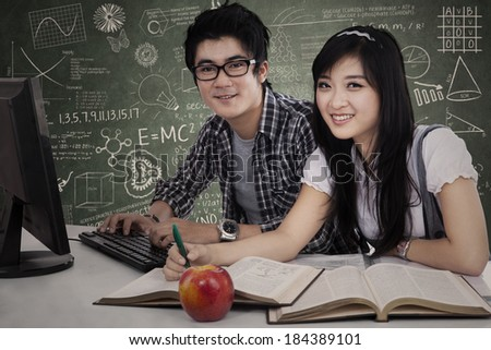Young Asian students studying together in class - stock photo