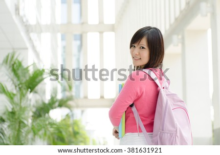 Young Asian teen student standing outside school campus building, holding file folder and smiling. - stock photo