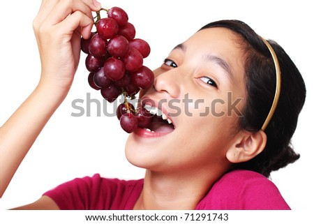 Young asian teenager eating a bunch of grapes. White background. - stock photo