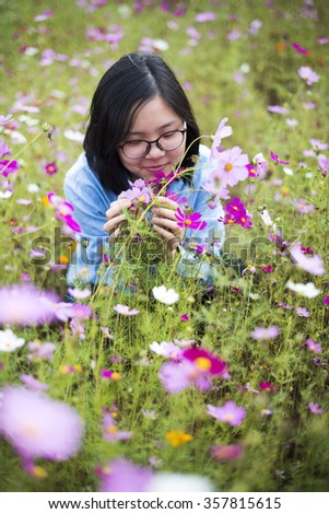 Young Asian teenager smell flowers at meadows. Photo with cool tone and vignetting.