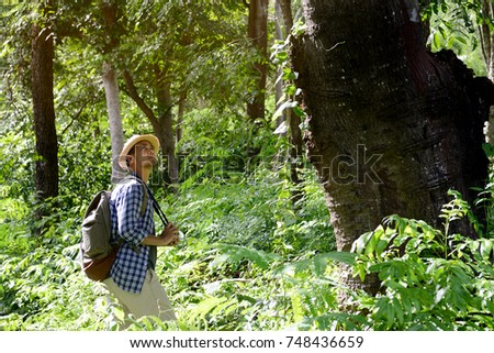 Young Asian tourist man with backpack traveling along rain forest