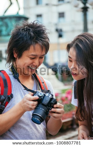 Young Asian Tourists Looking At The Photo