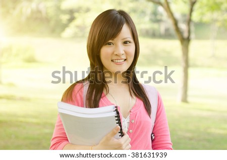 Young Asian university student standing on campus lawn, holding books and smiling. - stock photo