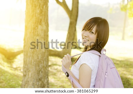 Young Asian university student standing on campus lawn, with backpack and smiling. - stock photo