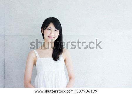 Young Asian woman against concrete wall - stock photo