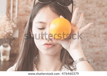 Young asian woman closing eyes and holding orange in hand, vintage tone