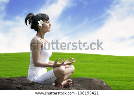 Young asian woman doing yoga exercise on a stone - stock photo