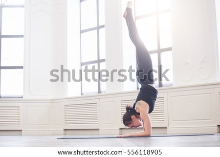 Young asian woman doing yoga pose and asana. Fitness girl enjoying yoga indoors in sport clothes, working out in gym class
