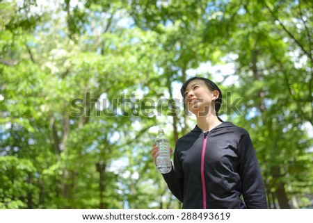 Young Asian woman drinking water during exercise. - stock photo