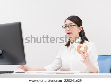 Young Asian woman eating a donut while working