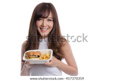 Young Asian woman eating burger and french fries on white background, unhealthy eating and diet concepts.