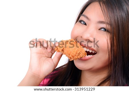 Young Asian woman eating fried chicken, on white background - stock photo