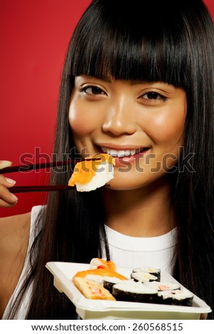 Young Asian woman eating sushi on red background. - stock photo