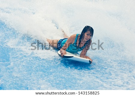 Young Asian woman enjoy body surf with flowrider