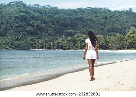Young Asian woman enjoying a summer day at the beach walking along the golden sand of a lush green bay away from the camera in a tropical island paradise - stock photo