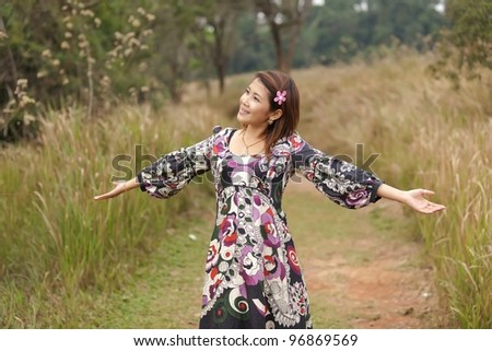 young asian woman enjoying breathing in nature, thailand - stock photo