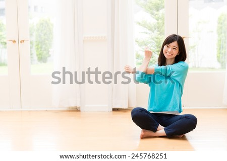 young asian woman exercising in the living room - stock photo