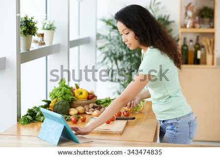 Young Asian woman following recipe in the digital tablet while cooking - stock photo