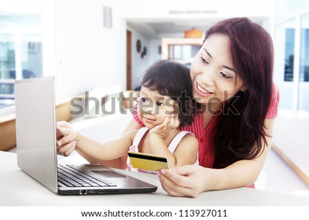 Young asian woman gives online shopping education to her daughter, shot at home - stock photo