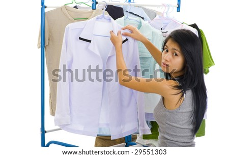 young asian woman hanging clothes, isolated on white - stock photo