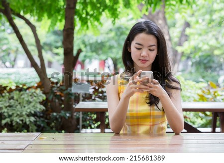 Young asian woman happily using a smart phone - stock photo