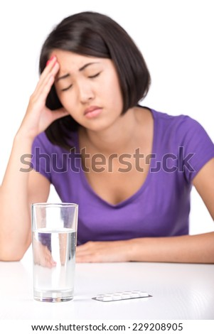 Young asian woman has headache. Pills and water on the table.
