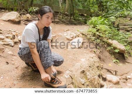 Young asian woman hiker stops to tie her shoe on a summer hiking trail in forest.