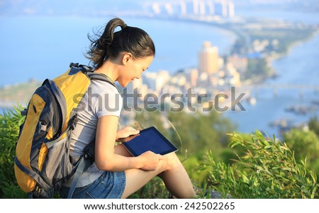 young asian woman hiker use digital tablet seaside mountain peak  - stock photo