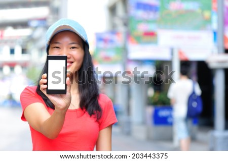 young asian woman hold blank smart phone on shopping street  - stock photo