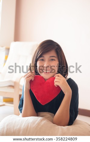 Young asian woman hold red heart soft toy. - stock photo