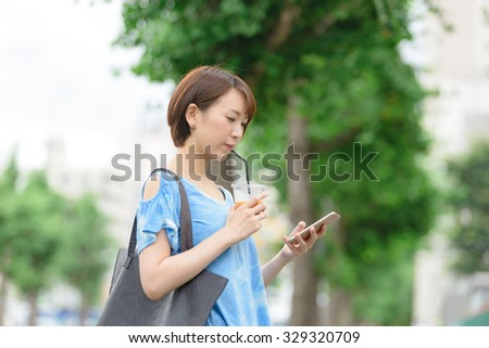 Young Asian woman holding a coffee cup and smart phone. - stock photo