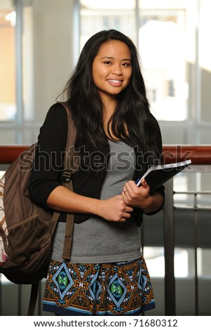Young Asian woman holding a copybook and with college buildings as background - stock photo