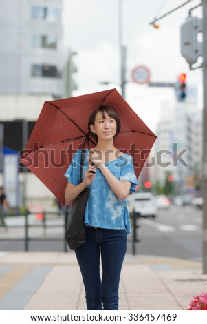 Young Asian woman holding an umbrella. - stock photo